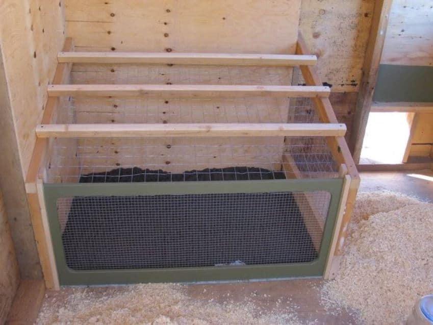 posatoio notturno su cassone raccogli-feci in rete (con sportello frontale a scorrimento) all'interno di un piccolo pollaio da giardino