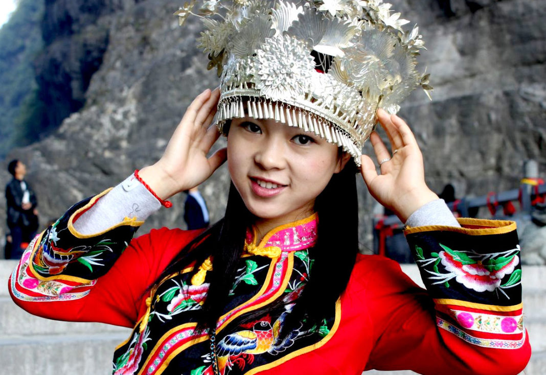 Ragazza cinese vestita a festa tradizionale durante il gioco del gallo