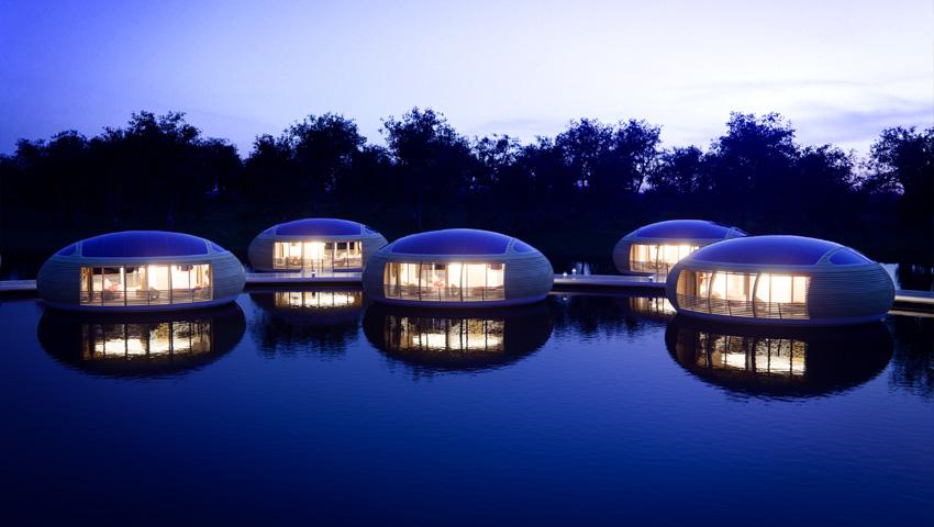 Suggestivo bordo lago con tante case-uovo galleggianti illuminate alla sera