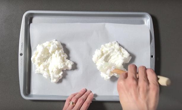 Creare le due nuvole sulla carta forno creando un alloggiamento centrale per il tuorlo
