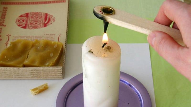 la pisalka con il piccolo serbatoio di cera d'api scaldato sulla fiamma