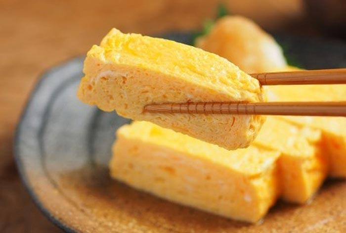 Tamagoyaki abilmente mangiato con le bacchette (hashi).