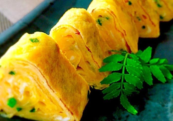 La manipolazione finale della forma della frittata Tamagoyaki con la stuoietta di bambù.