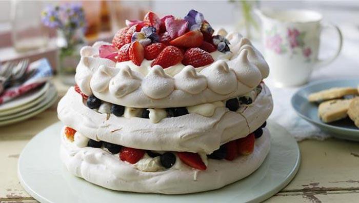 Torta Pavlova a tre strati con frutti di bosco e petali di fiori