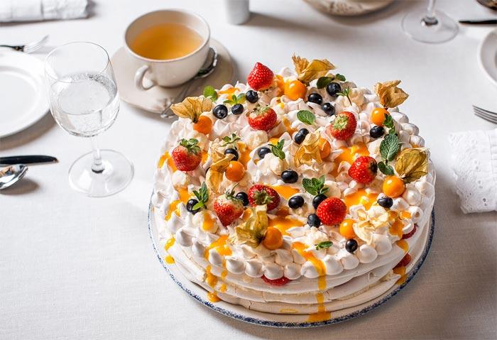 Torta Pavlova con fragole, mirtilli, alchechengi, foglie di menta e succo di mango
