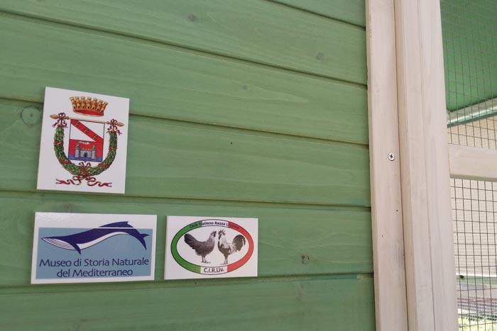"""Gli stemmi sulla """"Casa delle galline livornesi"""" (ancora da aggiungere il logo dell'Università di Pisa)."""