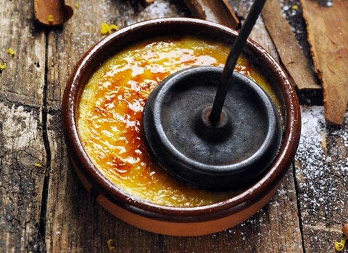 La caramellizzazione finale dello zucchero della Crème brûlée con il ferro incandescente tradizionale